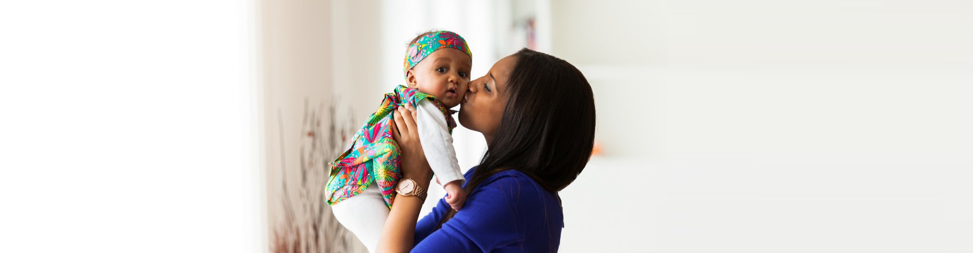 beautiful woman carrying and kissing the kid